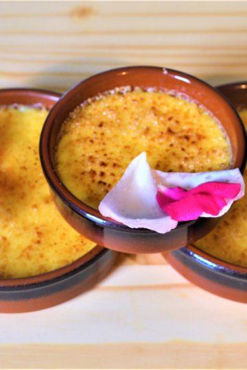 trois ramequins avec la creme brulee, petales de rose