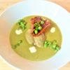 l'assiette avec la soupe verte, petits pois, taches de creme fraiche, tranche de chorizo