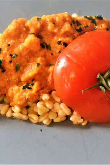 czubek pomidora zszypulka, polozony na rybie w sosie koloru pomaranczowego