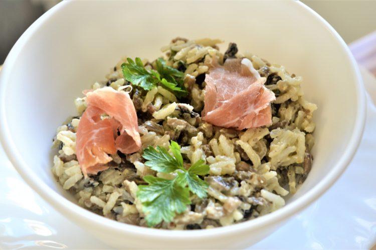 w bialej miseczce salatka z ryzem i pieczarkami, galazki pietruszki, kawalki szynki